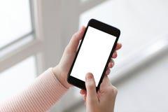 Mains de femmes tenant le téléphone avec le windo d'isolement de fond d'écran Photographie stock libre de droits