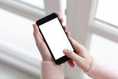 Mains de femmes tenant le téléphone avec le windo de fond d'écran Images libres de droits
