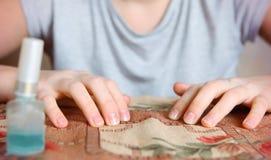 Mains de fille d'adolescent avec l'émail de manucure et d'ongle Photographie stock
