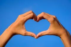Mains de fille dans la forme du coeur d'amour sur le ciel bleu Image libre de droits
