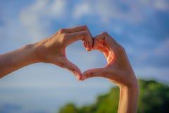 Mains de fille dans la forme du coeur d'amour sur le ciel bleu Photographie stock libre de droits