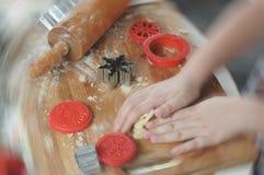 Mains de fille malaxant la pâte pour des biscuits de Noël photographie stock