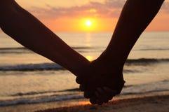Mains de fixation de couples au coucher du soleil Image libre de droits