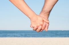Mains de fixation de couples sur la plage Image libre de droits