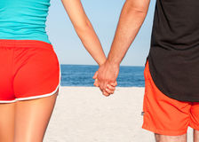 Mains de fixation de couples sur la plage Photographie stock