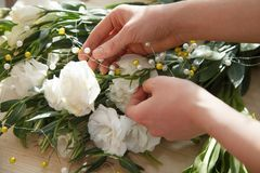Mains de fleuriste faisant le bouquet jaillir fleurs Images stock