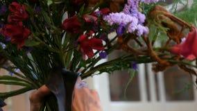 Mains de fleuriste de femme faisant une composition florale ou un bouquet des fleurs fra?ches clips vidéos