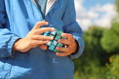 Mains de garçon avec le cube magique extérieur Photos libres de droits