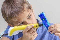 Mains de garçon créant avec l'avion bleu du stylo 3d photo libre de droits