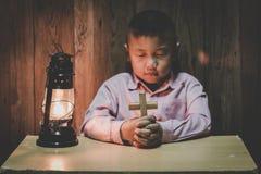 Mains de garçon tenant une croix sainte et priant à Dieu, enfant priant pour la religion de Dieu image libre de droits