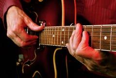 Mains de guitariste et haut étroit de guitare Images libres de droits