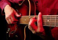 Mains de guitariste et haut étroit de guitare Photographie stock