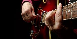 Mains de guitariste et haut étroit de guitare Photographie stock libre de droits