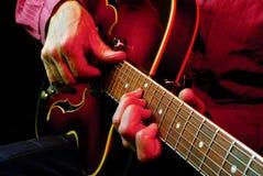 Mains de guitariste et haut étroit de guitare Image stock