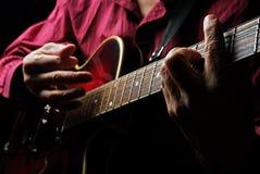 Mains de guitariste et haut étroit de guitare Images stock