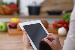 Mains de Haman utilisant le pavé tactile dans la cuisine Plan rapproché de femme faisant des achats en ligne en la tablette et la Photo libre de droits