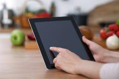 Mains de Haman utilisant le pavé tactile dans la cuisine Plan rapproché de femme faisant des achats en ligne en la tablette et la Images stock