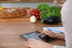 Mains de Haman utilisant le pavé tactile dans la cuisine Plan rapproché de femme faisant des achats en ligne en la tablette et la Images libres de droits