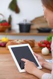Mains de Haman utilisant le pavé tactile dans la cuisine Plan rapproché de femme faisant des achats en ligne en la tablette et la Photographie stock
