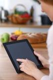 Mains de Haman utilisant le pavé tactile dans la cuisine Plan rapproché de femme faisant des achats en ligne en la tablette et la Photos libres de droits