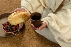 Mains de Jésus retenant le pain et le vin Image stock
