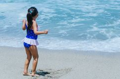 Mains de jeu de petite fille avec le sable images stock