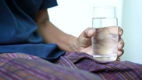 Mains de jeune femme tenant et mettant la médecine de comprimé de pilule aux mains du concept de dames âgées pour des soins de sa clips vidéos