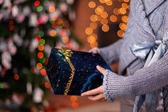 Mains de jeune fille offrant le beau cadeau de Noël enveloppé Photos stock