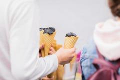 Mains de jeune homme avec la crème glacée fraîche délicieuse à la mode de charbon de bois dans le cône de gaufre pour des amis Co Photos stock