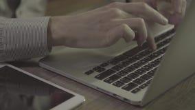 Mains de jeune homme utilisant le carnet sur une table clips vidéos