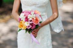 Mains de jeune mariée tenant le bouquet image libre de droits