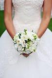 Mains de jeune mariée tenant le bouquet image stock