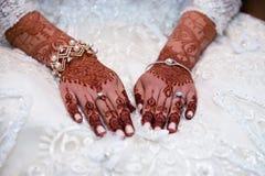 Mains de jeunes mariées couvertes en henné Photographie stock libre de droits