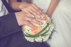Mains de jeunes mariés avec les anneaux et le bouquet de mariage Image libre de droits