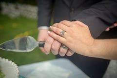 Mains de jeunes mariés coupant le gâteau photographie stock libre de droits