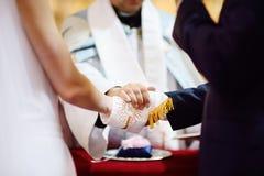 Mains de jeunes mariés enveloppées dans la soutane du prêtre photo stock