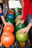 Mains de joueurs et système de retour de boule dans le bowling Images stock