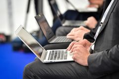 Mains de journalistes dactylographiant sur des ordinateurs portables pendant une conférence de presse images stock