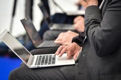 Mains de journalistes dactylographiant sur des ordinateurs portables pendant une conf?rence de presse photo stock