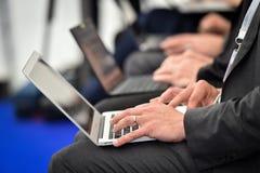 Mains de journalistes dactylographiant sur des ordinateurs portables pendant une conf?rence de presse photographie stock