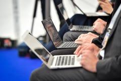 Mains de journalistes dactylographiant sur des ordinateurs portables pendant une conf?rence de presse photos stock