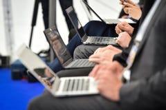 Mains de journalistes dactylographiant sur des ordinateurs portables pendant une conf?rence de presse images stock