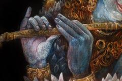 Mains de krishna de seigneur jouant la cannelure, détail avec le modèle de lotus Photographie stock