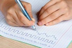Mains de l'écriture d'enfant dans le carnet Photos stock