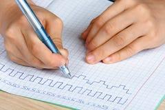 Mains de l'écriture d'enfant en copie-livre Images libres de droits