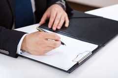 Mains de l'écriture d'homme d'affaires sur le presse-papiers Image libre de droits
