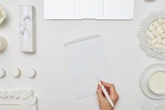 Mains de l'écriture femelle quelque chose sur un carnet vide Photo stock