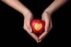 Mains de l'adolescence femelles tenant la pomme avec le coeur découpé Images stock