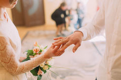 Mains de l'anneau de port de marié et de jeune mariée sur le doigt, cérémonie de mariage dans le bureau d'enregistrement, plan ra Images stock