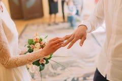 Mains de l'anneau de port de marié et de jeune mariée sur le doigt, cérémonie de mariage dans le bureau d'enregistrement, plan ra Photo libre de droits